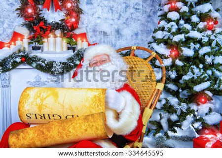 Kind Santa Claus sits in a snow-covered Christmas room and reads the scroll. Santa's mail, wish list.  - stock photo
