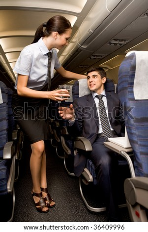 Kind stewardess giving glass of water to young businessman in airplane - stock photo