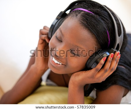 Kind woman listening to music and lying on sofa - stock photo