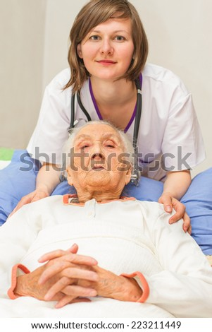 kind young female nurse caring for a very old female patient,in hospital - stock photo