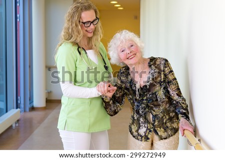 Kind Young Medical Assistant Assisting a Happy Elderly Woman Patient Walking at the Corridor in the Hospital. - stock photo