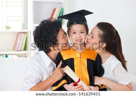 Kindergarten graduation. Asian family, grandparent and parent kissing grandchild on her kinder graduate day. - stock photo