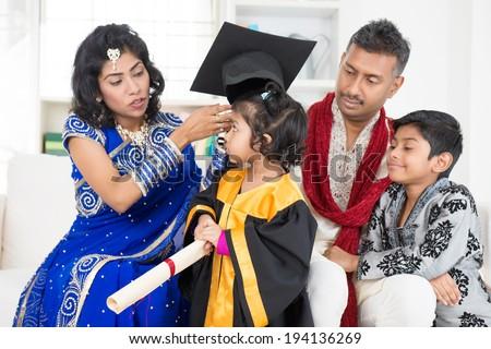 Kindergarten graduation. Asian Indian family, parents and children on kinder graduate day. - stock photo