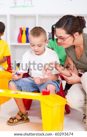 kindergarten teacher and preschool students - stock photo