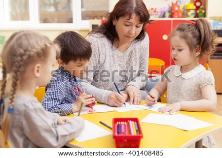 Kindergarten teacher, beautiful, mature caucasian woman, brown hair, teaches pupils drawing. Two little girls and a boy. - stock photo