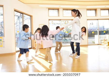 Kindergarteners and kindergarten teachers dancing in a circle