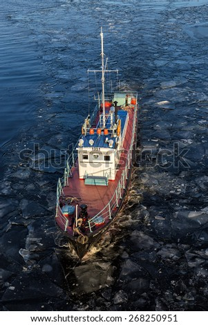 KINESHMA, RUSSIA - NOVEMBER 19, 2014: Small ship floats on the river Volga among ice floes in late autumn - stock photo