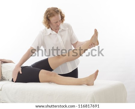 Kinesiologist or physiotherapist treating leg - stock photo