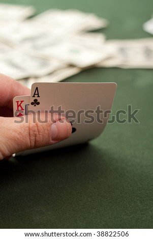 King and Ace on green poker table with hundred dollar bills in the background - stock photo