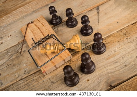 King  in a mousetrap surrounded by pawns, a concept - stock photo