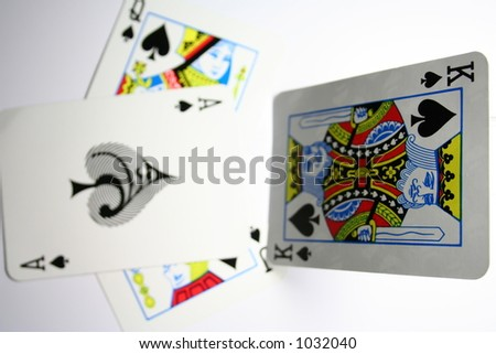 King of spades standing on top of other cards. Focus on the top end of the card. Shallow DOF. - stock photo