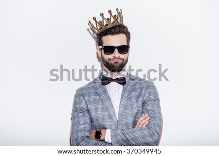 King of style. Sneering young handsome man wearing suit and crown keeping arms crossed and looking at camera while standing against white background - stock photo