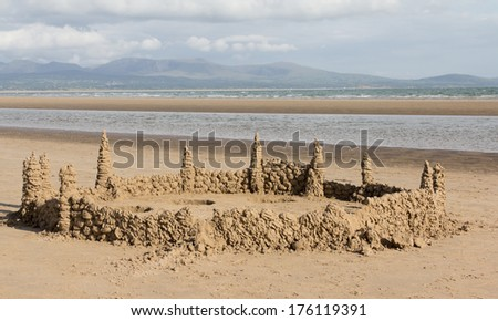 King of the castles. Large sand castle built on the sand on the beach at Newborough Anglesey,Wales with the Snowdonia mountain ranges as a backdrop. - stock photo