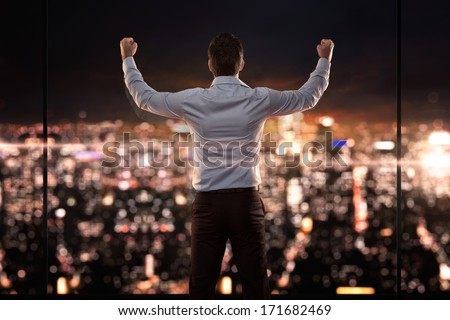 King of the world, young successful businessman in front of the city at night - stock photo