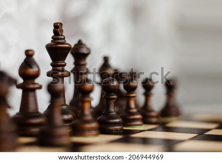 king, pawn and other figures on a chess board - stock photo