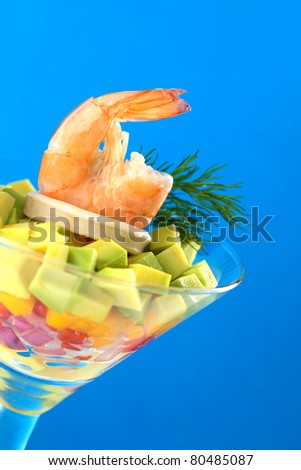 King prawn on a salad of onion, pepper, mango and avocado and a calamari ring, garnished with dill in a cocktail glass (Selective Focus, Focus on the king prawn) - stock photo