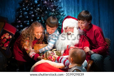King Santa Clause giving Christmas Presents to Happy Children in the Christmas Night - stock photo