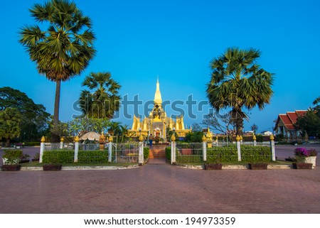 King Setthathirat statue and Pha That Luang stupa in evening.Pha That Luang, 'Great Stupa' is a gold-covered large Buddhist stupa in the centre of Vientiane, Laos. - stock photo