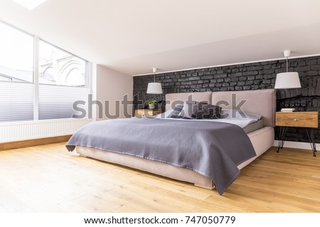 King-size bed between bedside cabinets and white lamps in cozy bedroom with view through window