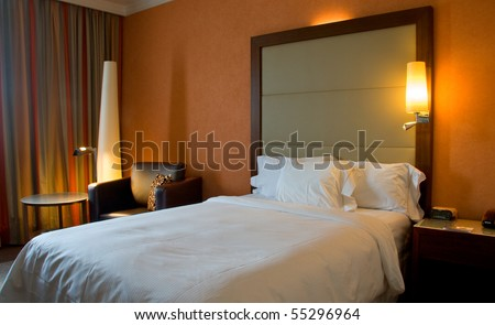 King-size bed with bedside table curtain and lamps - stock photo