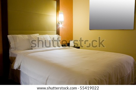 King-size bed with bedside table picture and lamps - stock photo