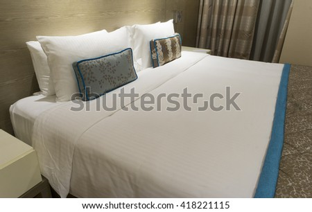 King sized bed in a business hotel room at night