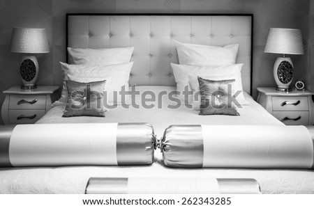 King sized bed in a luxuary hotel room, black and white - stock photo