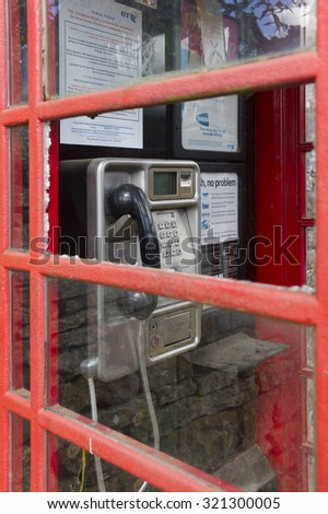 KINGHAM, UNITED KINGDOM - JUNE 19 2015 - Close-up of a red Telephone Booth with broken glass window in the city of Kingham, UK. - stock photo