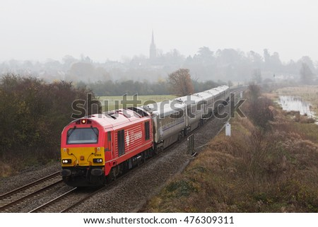 KINGS SUTTON, UK- NOVEMBER 20: A Chiltern operated express train heads toward Birmingham under a heavy winter sky on November 20, 2014 in Kings Sutton. Chiltern Railways operate over 336Km of UK rail.
