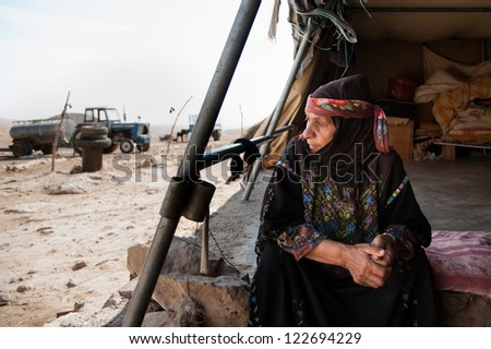 KIRBET AL FAKHEIT, PALESTINIAN TERRITORY - OCTOBER 17: A resident gazes from her tent, threatened with demolition by the Israeli military, in the South Hebron Hills of the West Bank, Oct. 17, 2012. - stock photo