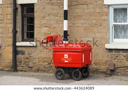 KIRKBY-IN-ASHFIELD, ENGLAND - JUNE 27: A Royal Mail high capacity trolley chained to a post. In Kirkby In Ashfield, Nottinghamshire, England. On 27th June 2016.