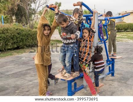 Kirkuk, Iraq - February 1, 2016: Syrian children fighting to play on sport machine inside park in Iraqi Kurdistan region - stock photo