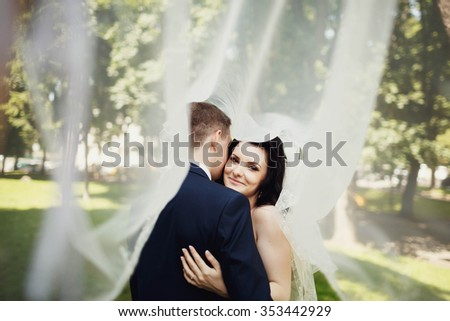 kiss of bride and groom near the wall - stock photo