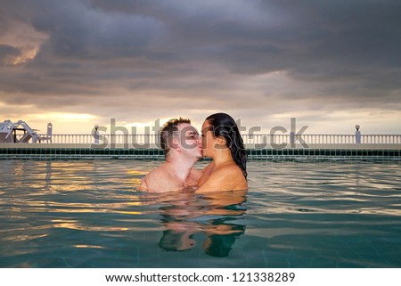 Kiss of loving couple in the swimming pool at sunset