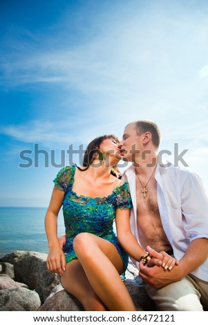 Kiss of loving couple sitting on beach stones against of blue sea landscape