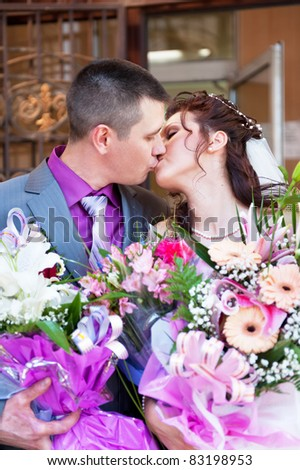 Kiss of the groom and the bride after registration of a marriage - stock photo