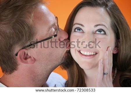 Kiss on cheek by man to a pretty woman - stock photo