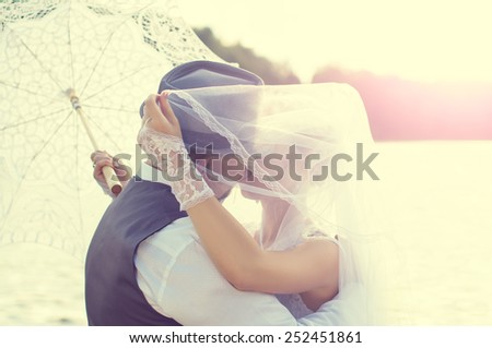 Kiss the bride and groom at sunset on a background of water - stock photo