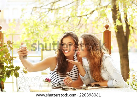 Kiss.Two cheerful girl  sitting on the cafe,  using a mobile phone.  - stock photo