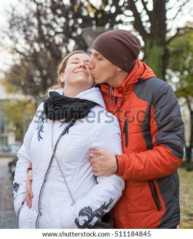 Kissing Caucasian young man and woman in white and red jackets, outdoor