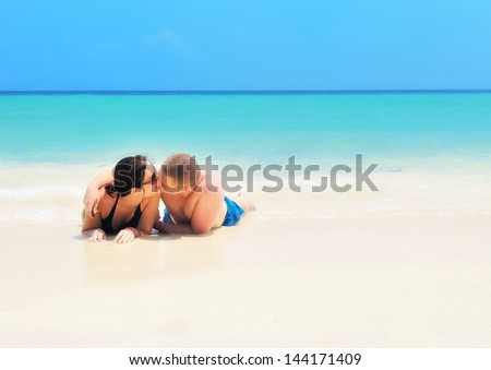 Kissing couple on the beach. - stock photo