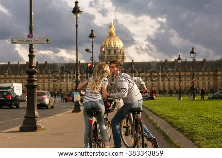 Kissing couple on the bikes on the summer Paris streets - stock photo