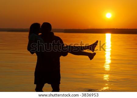 kissing couple on the evening beach dawn scenics - stock photo