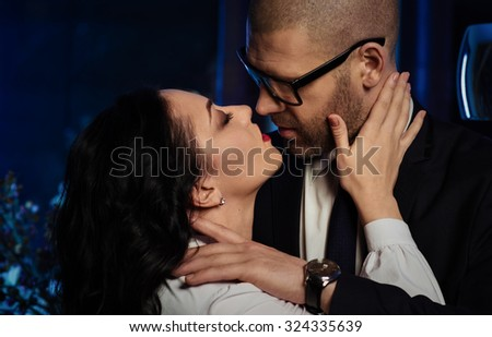 Kissing couple. Portrait of a sensual brunette and handsome businessman. Office romance concept  - stock photo