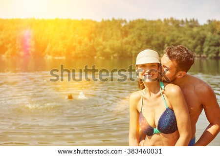 Kissing couple standing on the shore at a lake in summer - stock photo