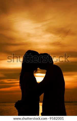 Kissing in Silhouette on the beach - stock photo