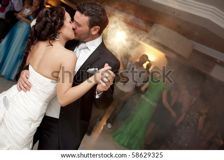 Kissing just married couple dancing in front of their unrecognizable friends. - stock photo