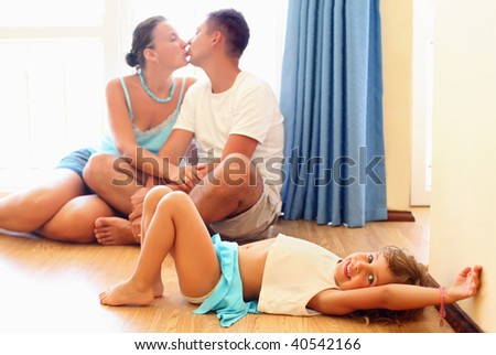 Kissing married couple with little girl lying on floor in cozy room