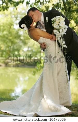 Kissing newlywed couple - stock photo