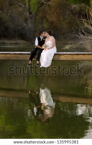 Kissing same sex newlywed on dock above lagoon - stock photo
